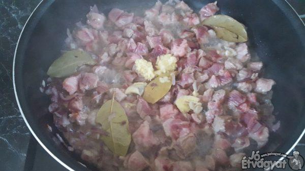 Amikor a lilahagyma megpirult, hozzáadjuk az apróra vágott sertéstarját, apróra zúzott fokhagymát és a babérleveleket