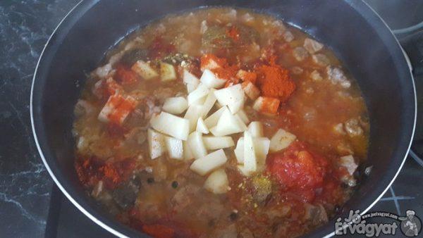 A hús amikor majdnem megfőtt, hozzáadjuk az apróra vágott burgonyát, szemes borst, őrölt pirospaprikát éa a paradicsomot