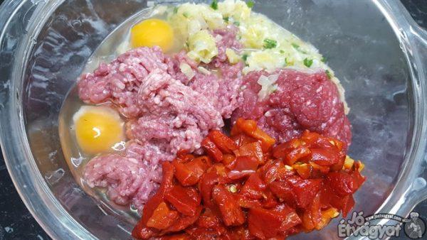 A ledarált húshoz hozzáadjuk a tojásokat, megpuhult póréhagymás masszát, sült papriká